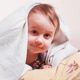Время ложиться спать (маленькая девочка лежа на кровати под крышками) Стоковые Фото