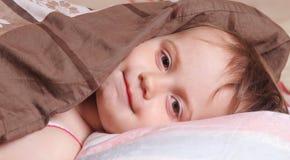 Время ложиться спать (маленькая девочка лежа на кровати под крышками) Стоковое Изображение