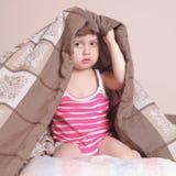 Время ложиться спать (маленькая девочка лежа на кровати под крышками) Стоковые Изображения