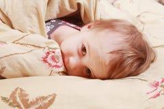 Время ложиться спать (маленькая девочка лежа на кровати под крышками) Стоковая Фотография