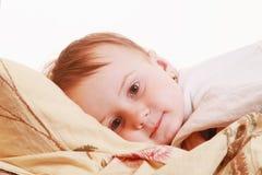 Время ложиться спать ребёнка (маленькая девочка лежа на кровати под крышками) Стоковые Фотографии RF