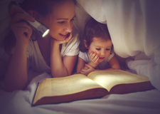 Время ложиться спать чтения семьи Книга чтения мамы и ребенка с flashl Стоковые Фотографии RF