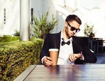 Время ожиданность помадка чашки круасанта кофе пролома предпосылки человек, бизнесмен в деловом костюме и чашка кофе смотря часы  Стоковая Фотография RF