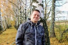 Время осени: человек в голубых джинсах представляя против фона леса березы осени Стоковая Фотография RF
