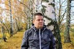 Время осени: человек в голубых джинсах представляя против фона леса березы осени Стоковые Фото
