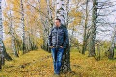 Время осени: человек в голубых джинсах представляя против фона леса березы осени Стоковые Изображения