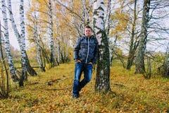 Время осени: человек в голубых джинсах представляя против фона леса березы осени Стоковое фото RF