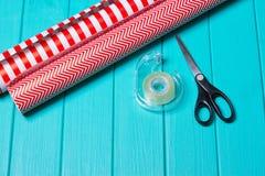 Время партии оборачивать подарка рождества с красочной бумагой, смычками ленты, ножницами a Стоковая Фотография RF