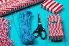 Время партии оборачивать подарка рождества с красочной бумагой, смычками ленты, ножницами a Стоковое Изображение