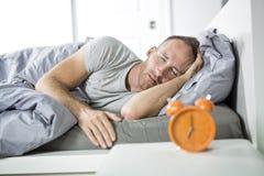 время поднять бодрствование Утомленный человек в кровати стоковое изображение