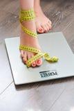 Время потерять килограммы при ноги женщины шагая на масштаб веса стоковые изображения rf