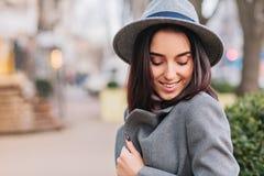 Время прогулки города очаровывать молодую стильную женщину в сером пальто, шляпе идя на улицу в городе Усмехаться с закрытыми гла стоковое фото