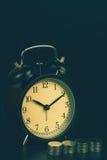 Время сбережений, будильник стоя при монетки изолированные на черной предпосылке С винтажным фильтром Стоковые Изображения