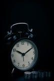 Время сбережений, будильник стоя при монетки изолированные на черной предпосылке С винтажным фильтром Стоковое Изображение RF