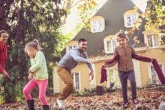 Время семьи Родители имеют игру с маленькими девочками снаружи Стоковое Фото