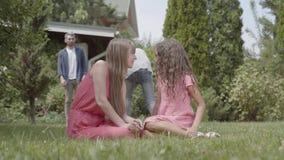 Время траты семьи портрета счастливое в саде совместно Мать и дочь сидя на переднем плане Отец и видеоматериал