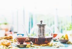 Время чая на таблице на окне Чашка и бак чая с тортом Стоковая Фотография