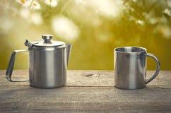 Время чая, чашка чая нержавеющей стали и чайник над деревянным столом o Стоковое Фото