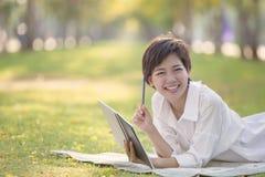 Время эмоции счастья расслабляющее азиатской более молодой женщины с книгой Стоковые Изображения