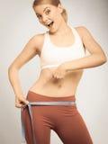 Время для потери веса диеты Подходящая девушка измеряя ее бедра Стоковая Фотография RF