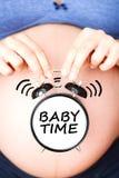 """Время It's иметь младенца с беременным животом и классическим будильником говоря """"baby  по буквам time†стоковое фото"""