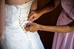 Вручает крупный план шнуруя вверх по корсету платья свадьбы стоковые фотографии rf