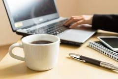 вручает печатать на машинке компьтер-книжки Чашка кофе, smartphone и компьтер-книжка на столе Стоковое фото RF
