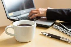 вручает печатать на машинке компьтер-книжки Чашка кофе, smartphone и компьтер-книжка на столе Стоковое Фото