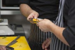 Вручает шеф-повара подготавливая блюдо персиков стоковые фотографии rf