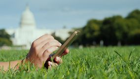 вручает smartphone На лужайке, на фоне капитолия в Вашингтоне Перемещение и исследование в США акции видеоматериалы