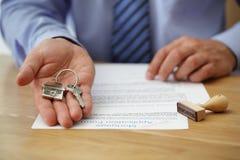 Вручать над ключами дома стоковое изображение