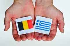 2 вручают владениям национальные флаги Германии (l) и Греции (r) Стоковое Фото