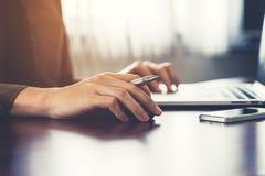 Вручите бизнесмена держа мышь и используя компьтер-книжку в офисе Стоковая Фотография