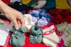 Вручите ботинки младенца взятия связанные шерстями теплые уютные стоковое изображение rf