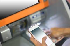 Вручите вводить кредитную карточку в atm держа умный телефон стоковые фотографии rf