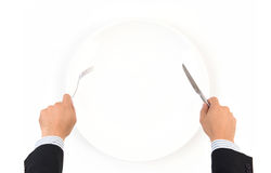 Вручите вилку и нож владением с белой плитой Стоковая Фотография