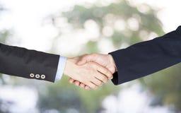Вручите встряхивание между бизнесменом и коммерсанткой на зеленой предпосылке Стоковое Изображение