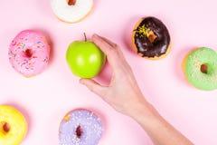 Вручите выбирать свежее зеленое яблоко окруженное мимо вкусных donuts еда принципиальной схемы здоровая Стоковые Изображения RF