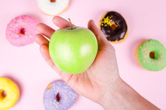 Вручите выбирать свежее зеленое яблоко окруженное мимо вкусных donuts еда принципиальной схемы здоровая Стоковое фото RF