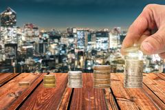Вручите выбранную монетку положенную на фонды монеток кучи с запачканным glowin стоковые фотографии rf