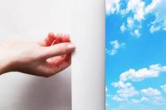 Вручите вытягивать край бумаги для того чтобы расчехлить, покажите голубое небо стоковые изображения rf