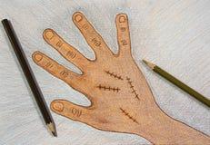 Вручите вычерченную правую руку с хирургической обветренной сутурой деревянными карандашами цвета на предпосылке на таблице, конц стоковое изображение rf