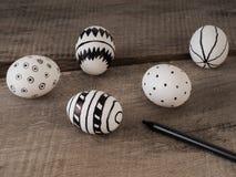 Вручите вычерченные пасхальные яйца с ручкой на деревянном столе стоковые изображения rf