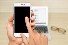 Вручите владение и касайтесь на белом Smartphone с предпосылкой компьтер-книжки стоковое фото rf