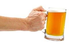 Вручите владению стеклянную кружку пива изолированную на белизне стоковая фотография