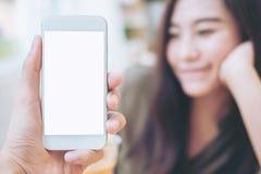 Вручите держать белый мобильный телефон с пустым белым экраном и запачкайте предпосылку стороны женщины smiley в современном кафе Стоковая Фотография