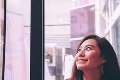 Вручите держать белый мобильный телефон с пустым белым экраном и запачкайте предпосылку стороны женщины smiley в современном кафе Стоковое фото RF
