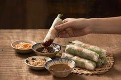 Вручите держать въетнамский блинчик с начинкой над шаром с окунать стоковые фотографии rf