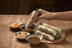 Вручите держать въетнамский блинчик с начинкой над шаром с окунать соевый соус стоковая фотография
