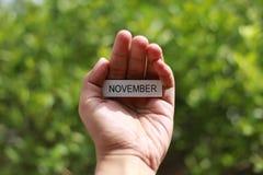 Вручите держать деревянную ручку с ` в ноябре ` слова на ем стоковая фотография